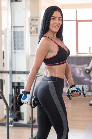 Photo pour Femme musculation avec matériel d'exercice dans le club de santé, portrait de femme fitness posant dans une salle de sport - image libre de droit