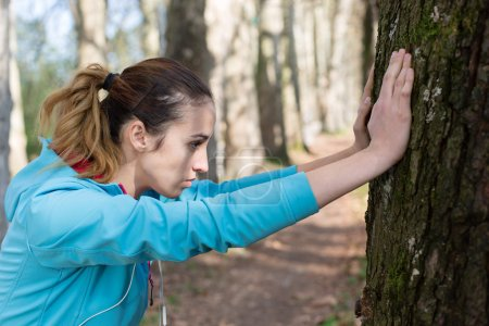 Healthy fitness woman resting in woods after a trail run. vitali
