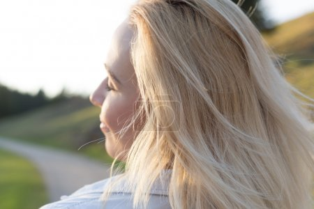 Blond woman in a field at sunset