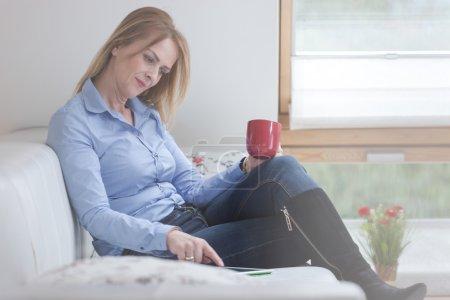 Adult woman holding tablet and mug
