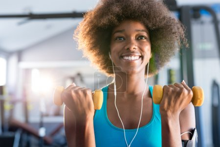 woman working out in gym with dumbbells