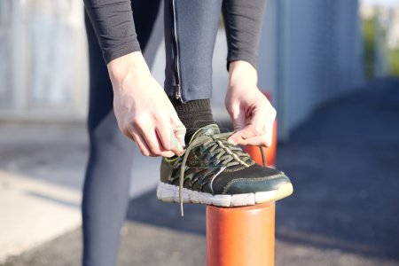 Running and jogging exercising concept. Man tying laces before running