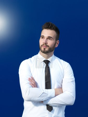 Businessman in front of blue background smiling
