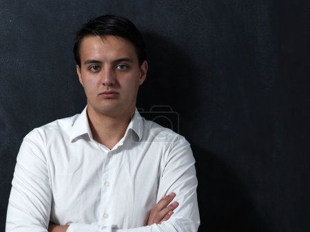 Portrait of a serious young man standing against chalkboard