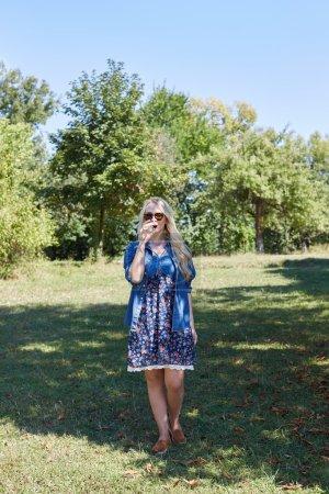 Blondine trinkt Wein bei Picknick in der Natur