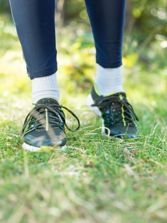 Healthy lifestyle sports man tying shoelace before running in na