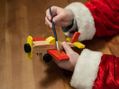 Santa Claus sitting in his workshop painting a toy airplane. Hor