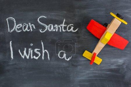 Dear Santa is written on a blackboard and christmas gift