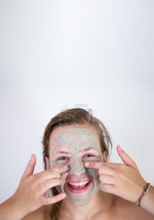 Beautiful young woman with facial mask, beauty treatment