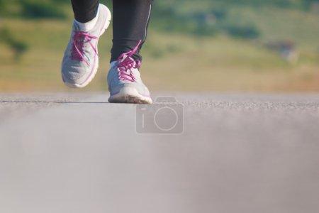 Female athlete runner. closeup on shoe. woman fitness sunset jog