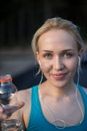 Fit blonde drinking from her water bottle on a sunny day