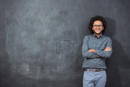 pensive young African American man standing against a blank chal