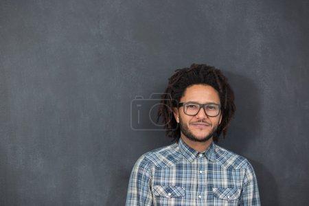 Foto de Joven guapo afroamericano hombre gesto emocional posingon pizarra, hipster en pizarra - Imagen libre de derechos