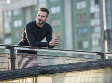 Portrait of Sport and fitness runner man resting on bridge after