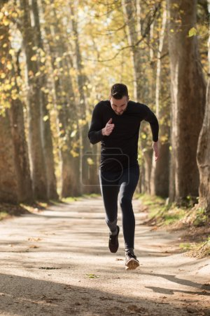 Photo for Runner man running on road training sprint for marathon run. Sporty fit caucasian male fitness sport model working out outside in full length. - Royalty Free Image