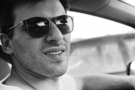 side view of a young man driving his convertible car