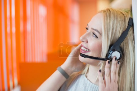 Portrait of support phone operator in headset at workplace. To p