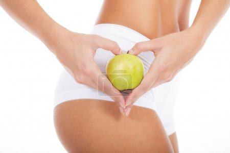 young woman in white underwear holding green apple
