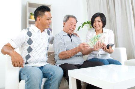 Photo pour Asiatique homme senior et enfants calcul argent chez eux - image libre de droit