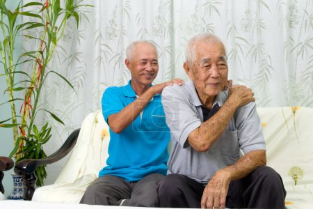 Photo for Asian old man shoulder pain, sitting on sofa , son massaging father shoulder. Chinese family, senior retiree indoors living lifestyle at home. - Royalty Free Image