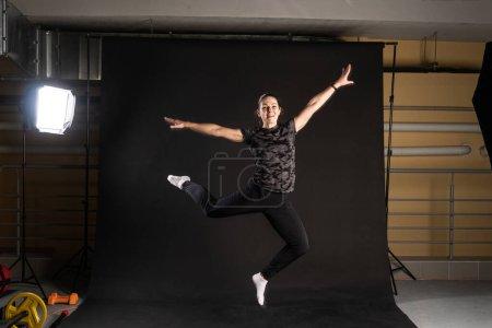 Photo pour Fitness dans le studio a rebondi sur les bras. Engagé dans le sport sur fond noir Happy - image libre de droit