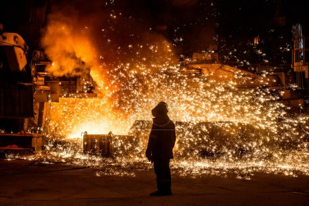 Steelworker near a blast furnace with sparks