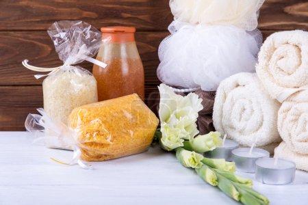Photo pour Spa serti de fleurs, sel de mer dans les paquets, gel douche, serviettes, scrubs et wisp sur table en bois blanc et fond en bois marron - image libre de droit
