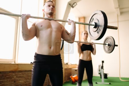 people lifting barbells