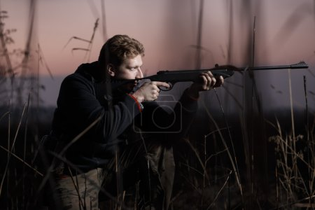 Huntsman with rifle at field