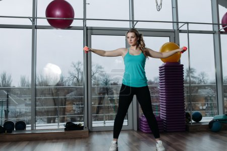 Photo for Beautiful sportswoman doing exercise for deltoid with dumbbells in fitness center - Royalty Free Image