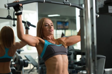 Photo for Athletic woman doing exercises on training apparatus - Royalty Free Image