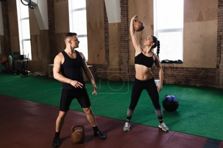 Man and woman training kettle bells