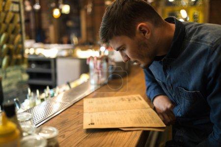 Photo pour Jeune visiteur lecture menu au bar dans un café - image libre de droit