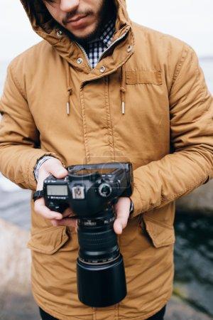 Photo pour Un homme méconnaissable tenant une caméra près de la mer - photo recadrée - image libre de droit