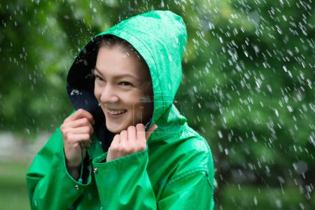 Woman in raincoat smiling at rainy day