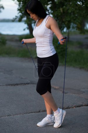 Attractive young woman skipping in the park