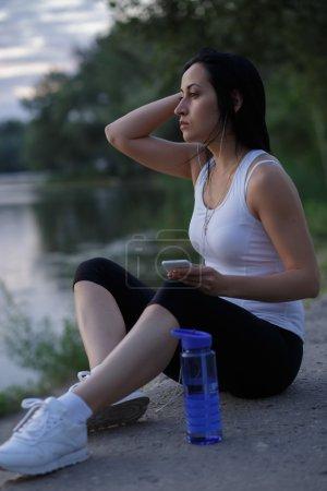 Photo pour Femme coureuse écouter de la musique après l'entraînement et en regardant le coucher du soleil près de l'étang - image libre de droit