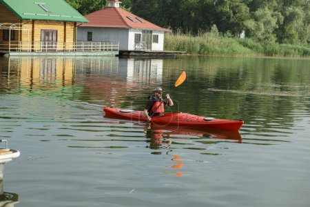 Man boating in red canoe at river pier at summer day