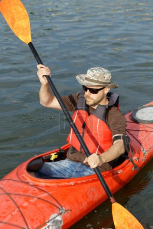 Photo for Man boating in red canoe in river at summer day - Royalty Free Image