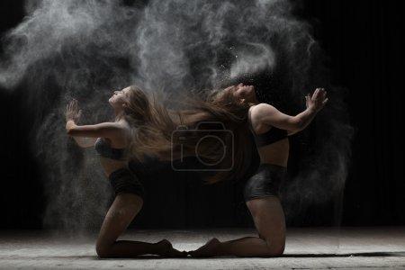 Photo pour Deux ballerines assises et saupoudrer de farine sur fond noir - image libre de droit