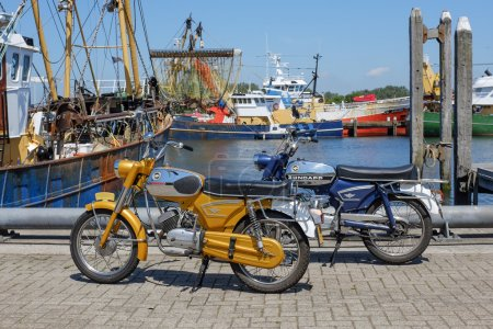 Two vintage Zundapp mopeds parked in a harbour.
