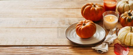 Photo pour Table de service de jour de Thanksgiving avec assiette, taleware, citrouilles et feuilles sur fond en bois, espace de copie, vue du dessus, bannière - image libre de droit