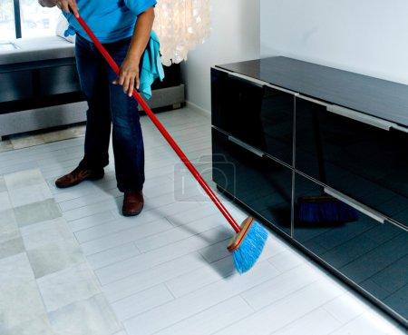 Maid sweeping bedroom floor
