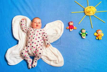 Child dressed in a Catsuit lying on a towel on the...