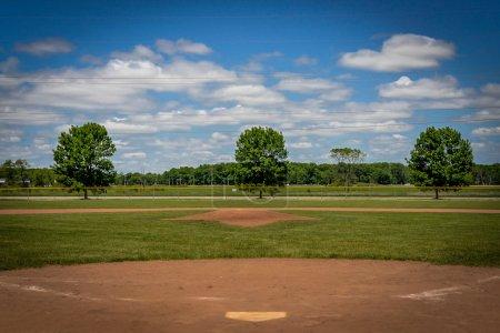 Photo pour Vides de terrain de baseball avec ciel bleu et nuages blancs pelucheux - ressemble à champ de rêves - image libre de droit