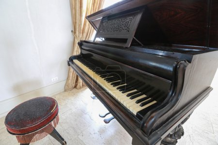 Piano classic with wooden chair in the room.