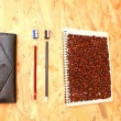 Coffee beans on a notebook, stylish black wallet w...