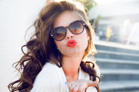 Photo for Closeup portrait woman with sunglasses and red lips looking in camera, air kiss - Royalty Free Image