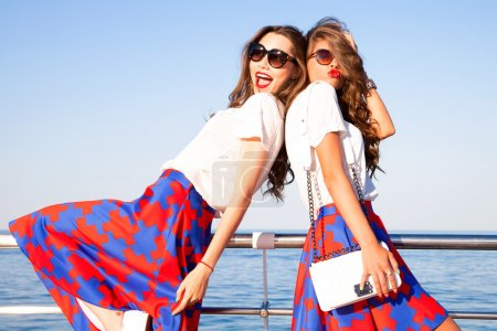 Outdoor lifestyle portrait of two best friends hipster girls wearing stylish bright outfits, denim shorts and glasses, going crazy and having great time together.Laughing and send kiss,lovely friends