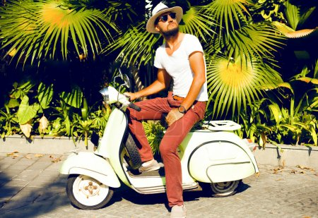 Photo for Full length portrait of a handsome young man enjoy his days, ride vintage scooter on the city, Casual man posing outdoor on the street, palms background. Street style, mans fashion. hand watch, mans hat - Royalty Free Image